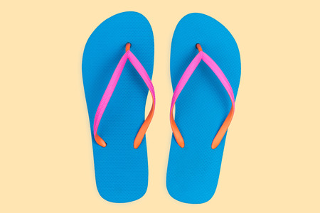 Blue flip flops isolated on yellow background. Top view