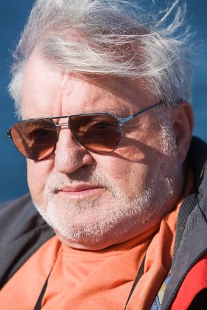 Senior man wearing sunglasses, wind, outdoors, close-up Stock Photo - 9374154