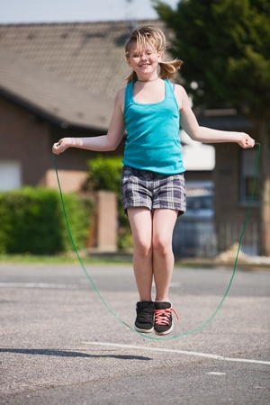 skipping: Young girl jumping rope outdoors