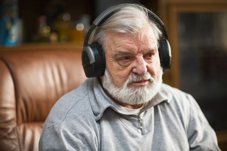 Senior man at home listening to music with headphones Stock Photo - 9423061