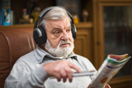 Senior man at home wearing headphones, holding magazine and remote control photo