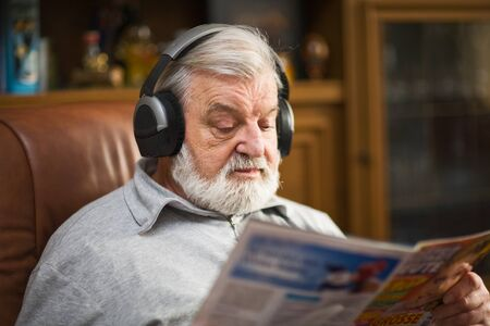 Senior man at home wearing headphones, reading magazine Stock Photo