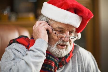 wearing santa hat: Senior man wearing Santa hat and using mobile phone