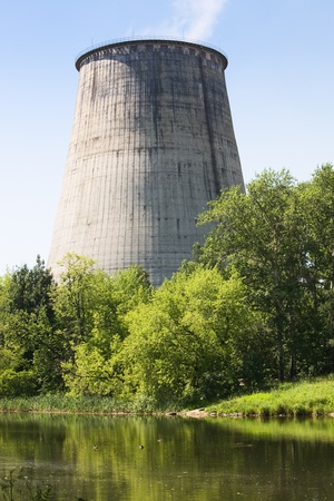 cooling tower: Cooling tower with water and trees in foreground