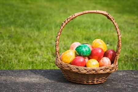 Basket full of Easter eggs on a stone slab photo