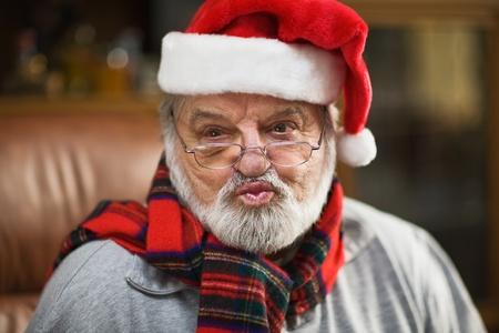 wearing santa hat: Senior man wearing Santa hat and blowing a kiss