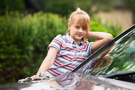 Portrait of young girl washing car  photo