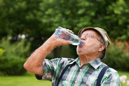 Senior man drinking bottled water photo