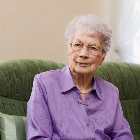91 years old woman sitting on couch in her living room, portrait photo