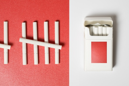Pack of Cigarettes on white and some cigarettes on red paper background photo