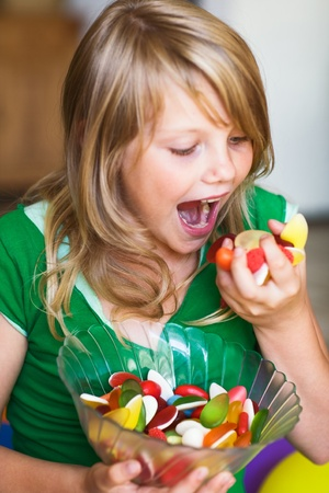 Girl eating sweet soft candies photo