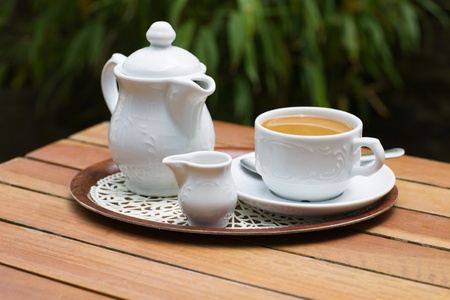 open air: White Coffee Pot on Table in Open Air Stock Photo