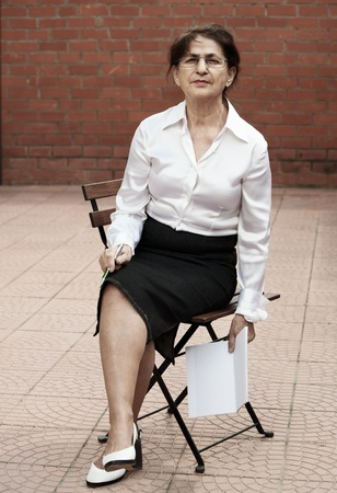 Senior woman in businesswoman look sitting on garden chair, holding pen and notebook photo
