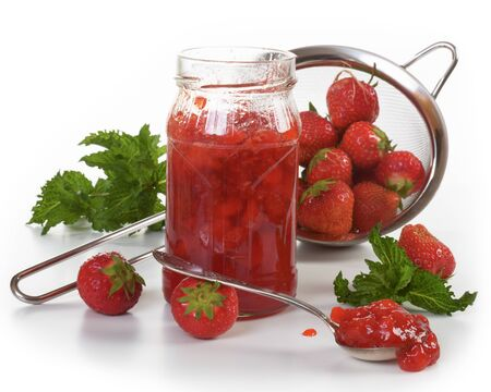 a colander: Jar of strawberry jam and fresh strawberries in a colander