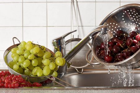 strainer: Fresh cherries being washed in a strainer