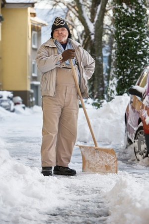 Senior Man Standing with Snow Shovel