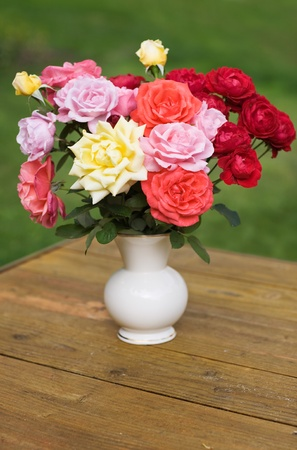 bunch of red roses: Porcelain pot with colorful roses Stock Photo