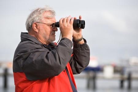 75s: Senior man looking through binoculars