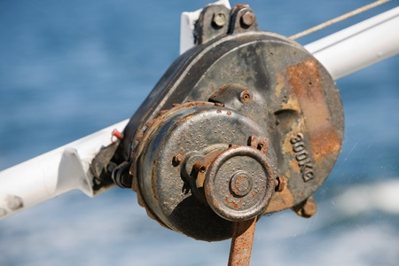Rusty old pulley with cobweb on a ship photo
