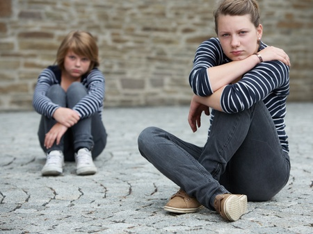 hugging knees: Teenage girls sitting on grounds, turned away from one another Stock Photo