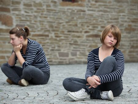 sweater girl: Teenage girls sitting on grounds, turned away from one another Stock Photo