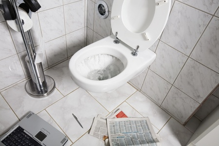 Newspaper, laptop and pen on floor by toilet photo