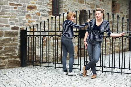 closed society: Two girls standing in front of closed gate Stock Photo