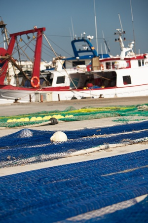 dockside: Nets laid out to dry on dockside, fishing boat on background, Majorca, Spain