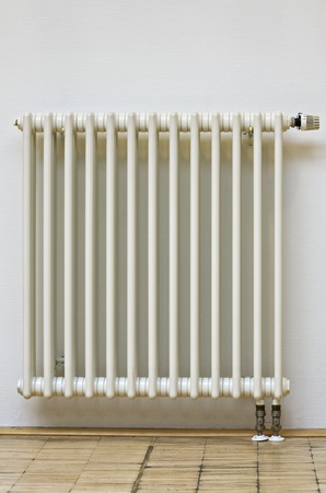 Close-up of home radiator with thermostat