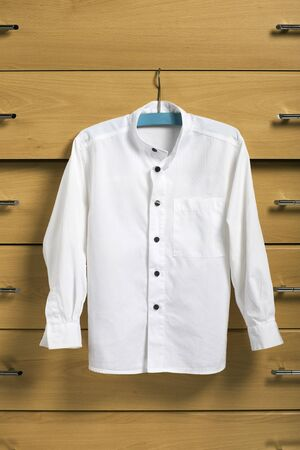 shirts on hangers: Child white shirt on blue hanger