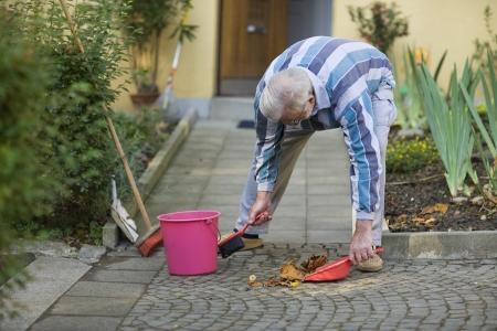 clean street: Senior is sweeping his sidewalk in autumn