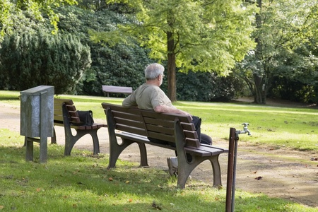 old man sitting: Senior man relax on a bench in park