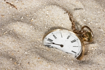 Antique golden watch lost in the sand photo