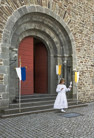 A young girl in white at her first communion photo