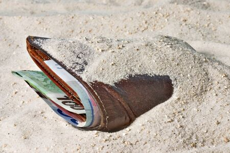 bury: Wallet with money lost in the sand