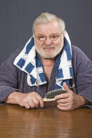 Senior in bathrobe with towel and hair brush after bath photo