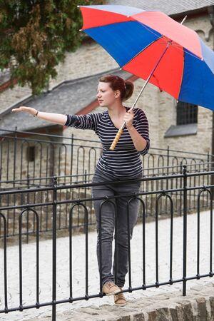 Teenage girl with umbrella waiting for rain photo
