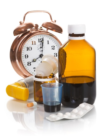 Alarm clock and medicine on white background