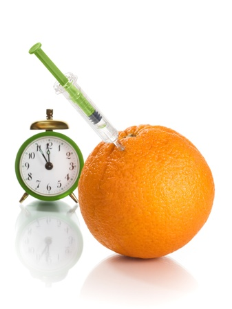 Orange with syringe and alarm clock photo