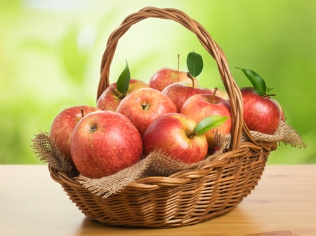 apples basket: Jonagold apples in a basket on wooden table against garden background Stock Photo