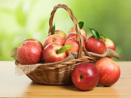 Jonagold apples in a basket on wooden table against garden background Stockfoto