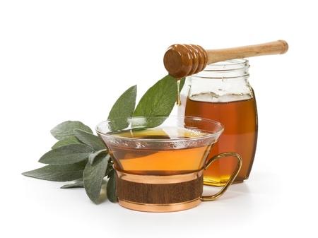 サルビアと白い背景の上の蜂蜜とハーブティー