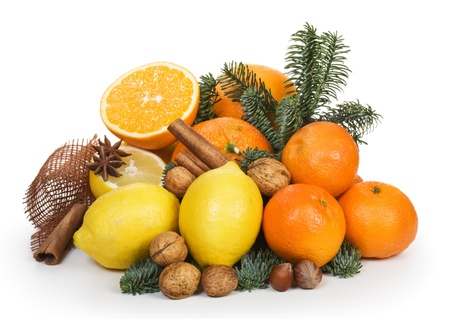 Citrus fruits, nuts, spices and branch of blue spruce on white background photo