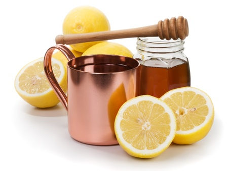 Copper cup of hot lemon drink, honey and fruits on white background photo