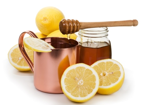 Copper cup of hot lemon drink, honey and fruits on white background