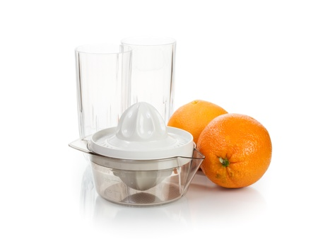 Juicer, ripe oranges and two glasses on white background