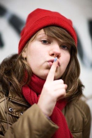 Teenage girl wearing red knit hat and holding finger with blue nail paint to lips photo