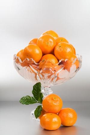 crystal bowl: Crystal glass footed bowl of orange mandarins on silver background