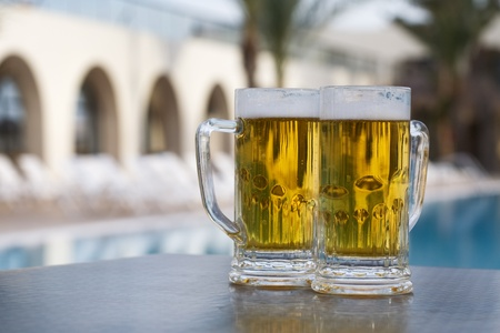 Two beer mugs by swimming pool in tropical resort photo