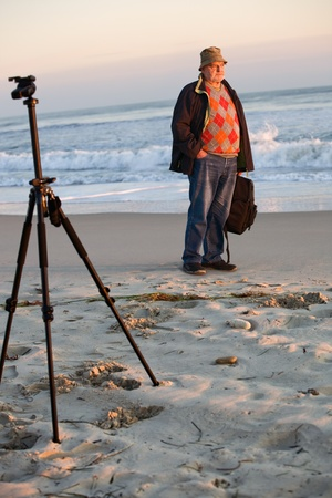 one senior man only: Senior photographer standing on the beach in early morning sun highlights